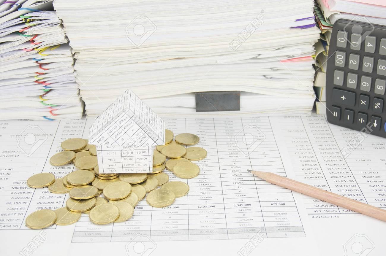 maison sur les pièces d'or et un crayon sur le compte de la finance