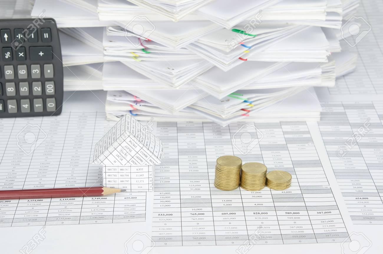 maison et crayon brun avec des tas de pièces d'or sur le compte de