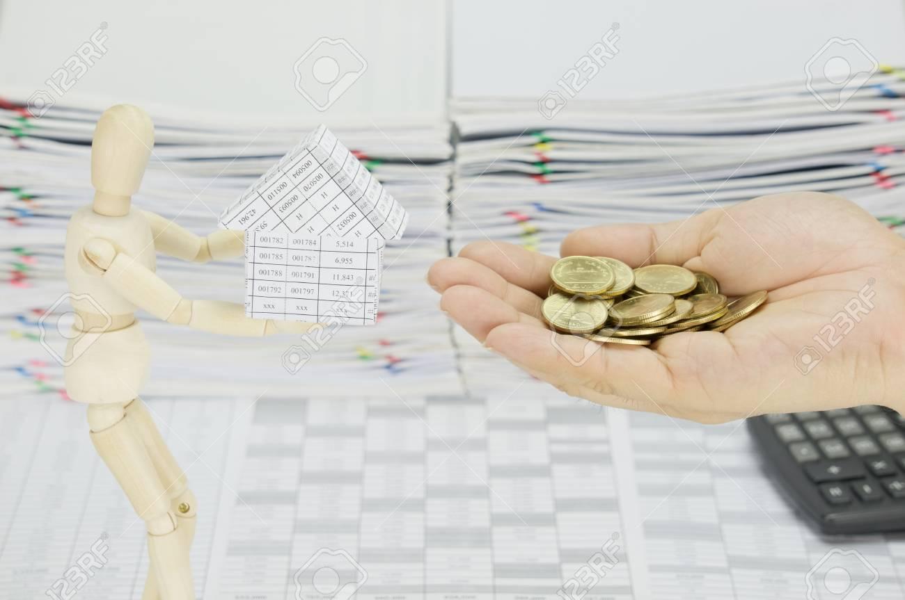 l'homme tenant des pièces d'or pour acheter une maison de mannequin