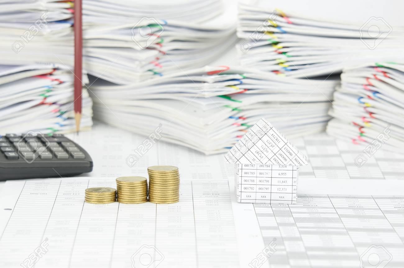 maison et étape pile de pièces d'or sur le compte de la finance ont
