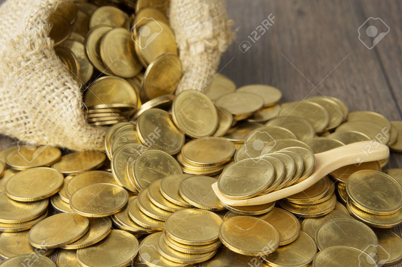 Close up gold coins in wooden spoon with brown sack of gold coins