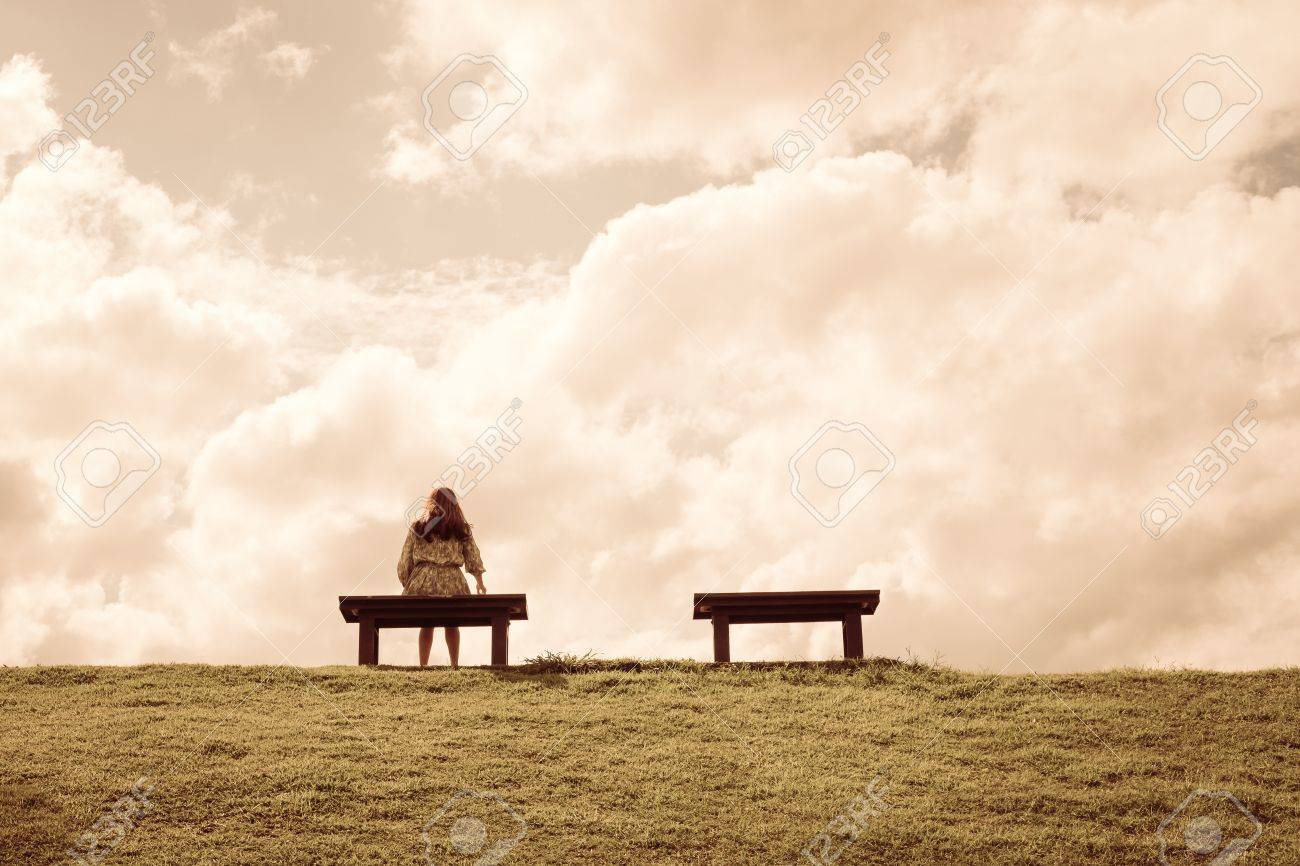 A women sitting alone on a bench waiting for love alone concept stock photo