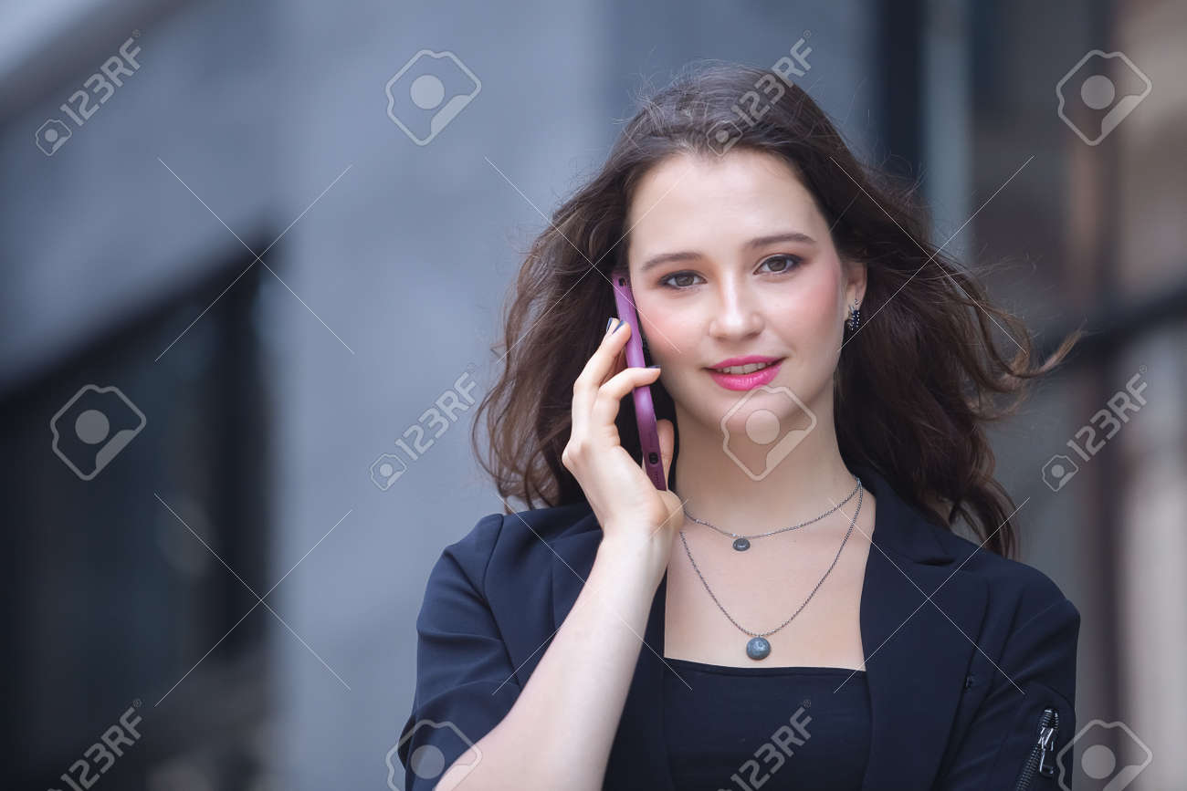 businesswoman calling on the mobile phone walk on city street. - 165832983
