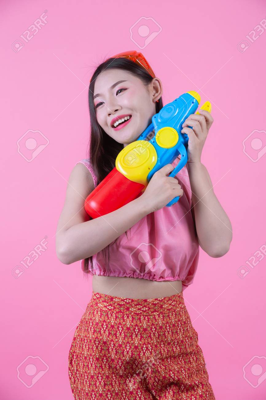 A woman dressed in a traditional Thai folk clothes holding a water gun on a pink background. - 120398354