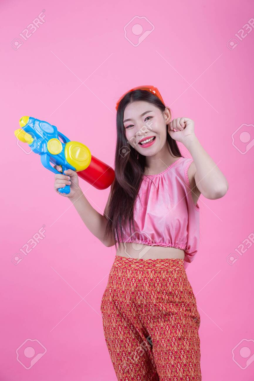 A woman dressed in a traditional Thai folk clothes holding a water gun on a pink background. - 120398357
