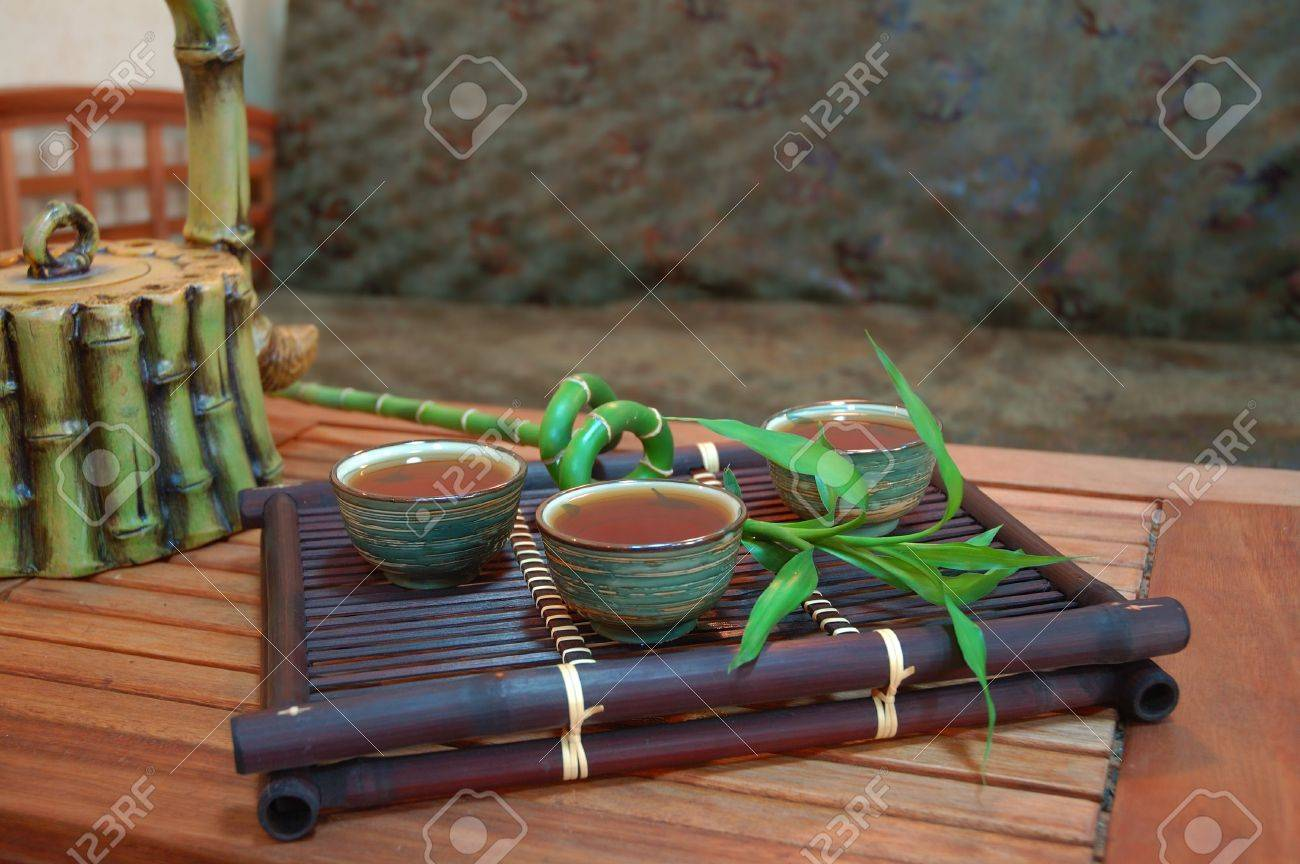 chinese tea in antique bowls with bamboo and teapot. interior