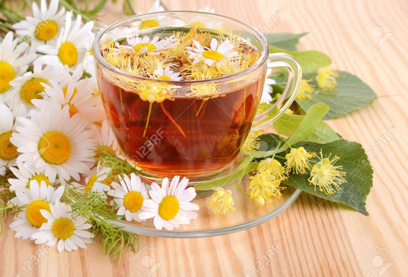 Herbal tea with linden and camomile flowers on a wood table background Stock Photo - 21061951