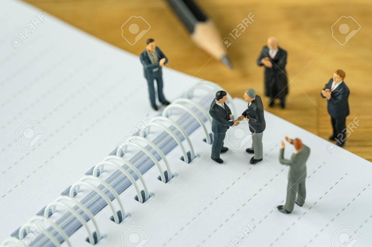 Miniature people: Small figure businessmen handshaking and others clapping on notebook and pencil as business agreement concept. - 80001754