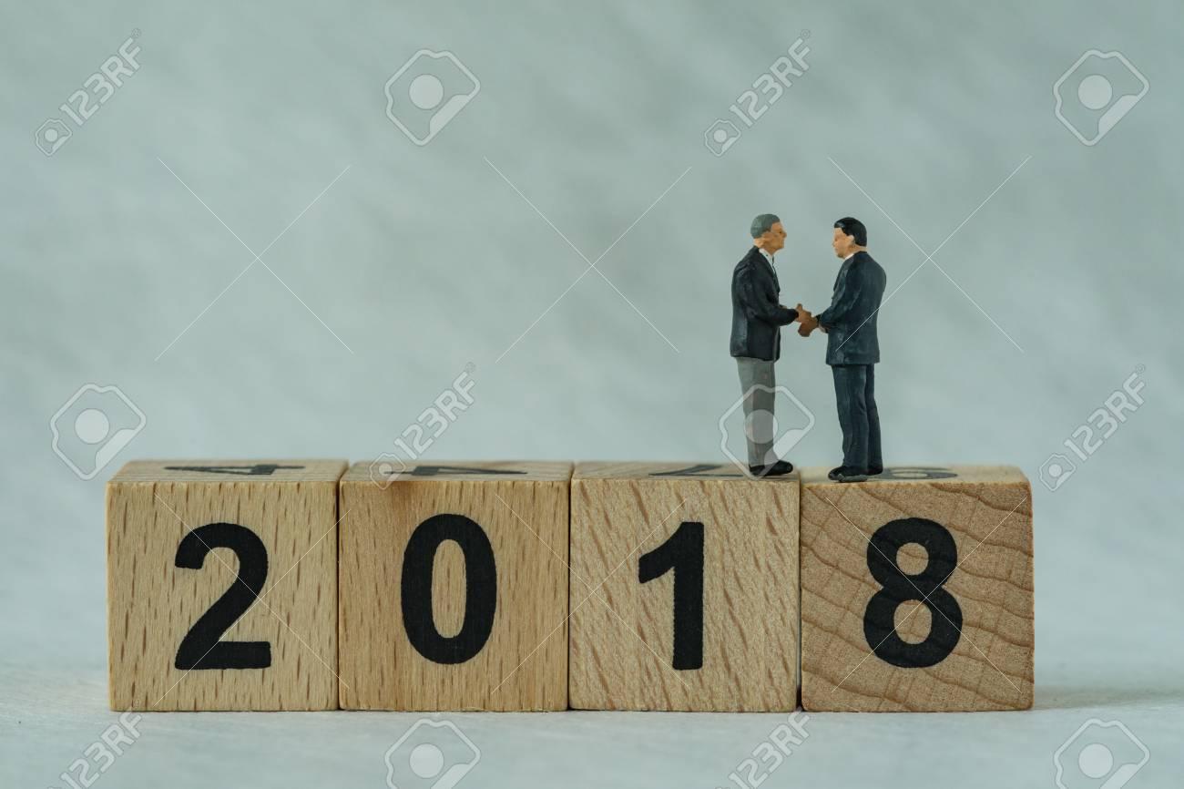 Miniature Businessmen Handshaking And Standing On Wooden Block