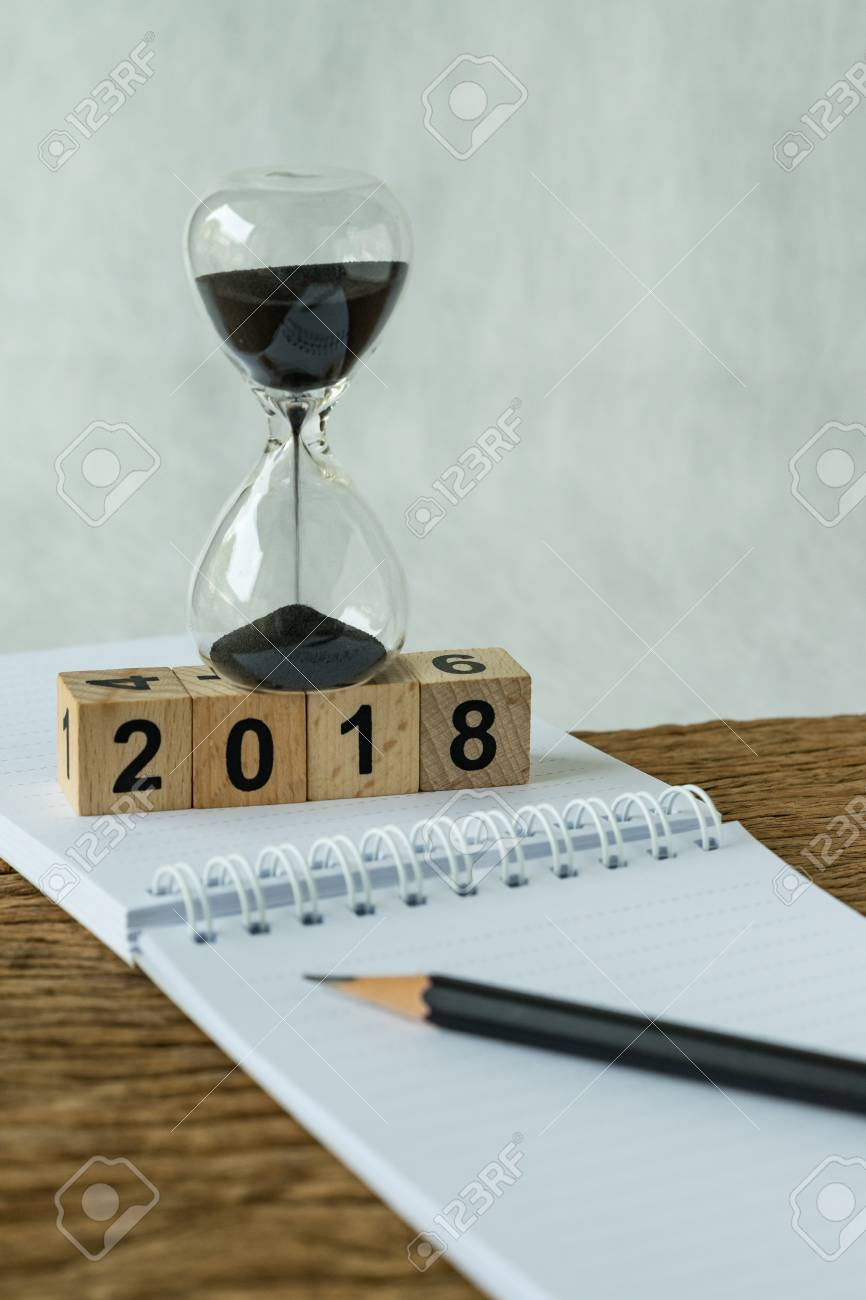 new year 2018 goals, target or checklist concept as number 2018 wooden cube block with sandglass and white paper note with pencil on wooden table. - 89349729