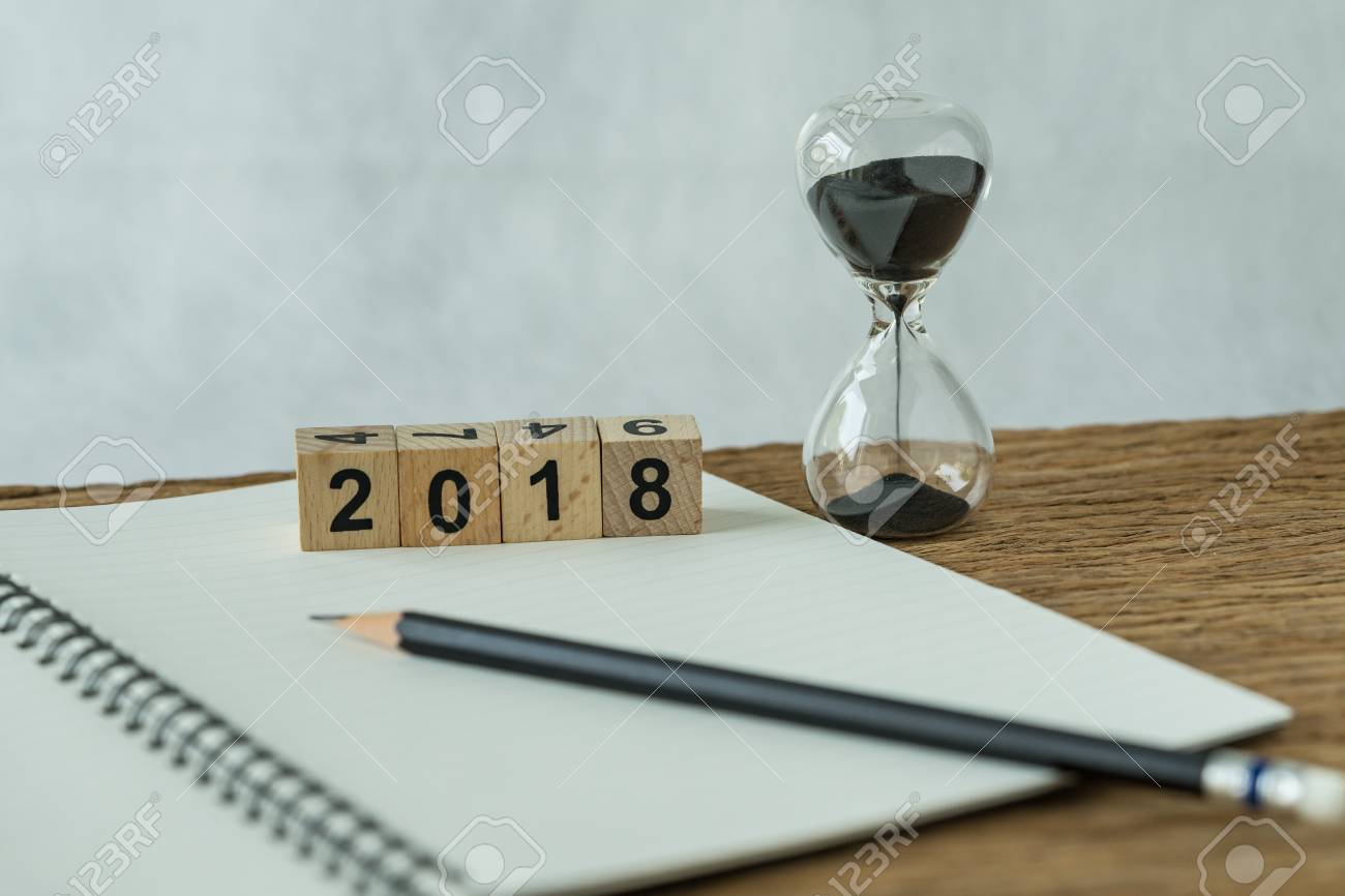 new year 2018 goals, target or checklist concept as number 2018 wooden cube block with sandglass and white paper note with pencil on wooden table. - 89432100