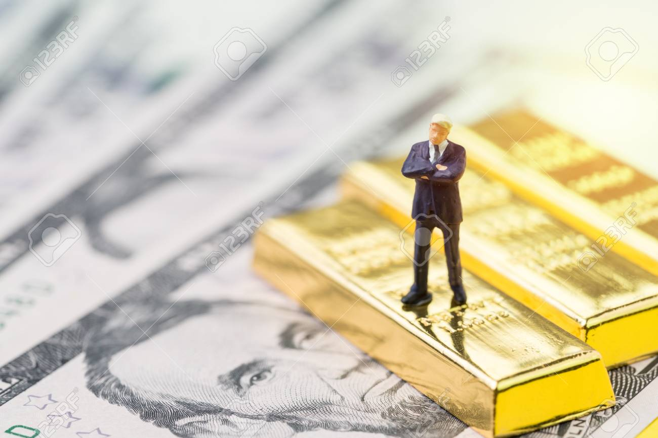 Success in investment, wealth management or financial crisis safe haven concept, miniature people businessman standing on gold bar, bullion or ingot stack on US dollar banknote money. - 100768448