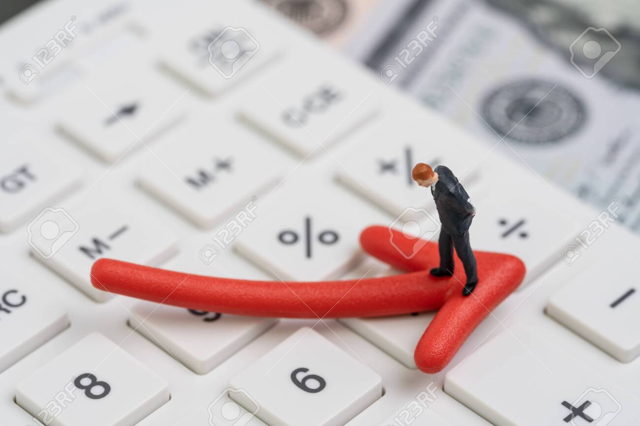 Economic recession, bear stock market or financial crisis concept, miniature businessman standing on red pointing down arrow on white calculator with background of US dollar banknote money. - 129454293