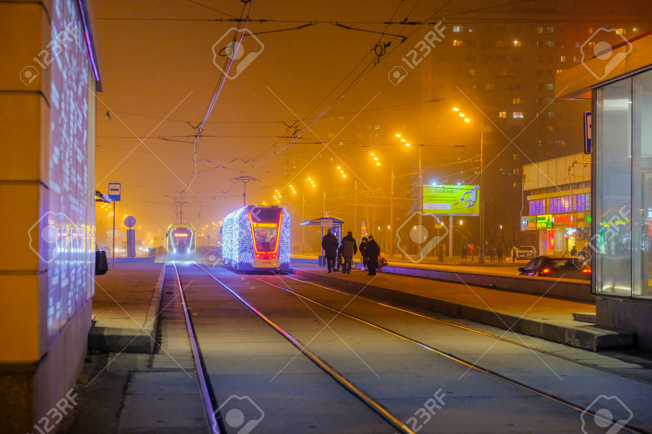 Moscow.Russia. December 26, 2019. Trams in the fog lit by a network of LEDs arrive at a bus stop with passengers. Environmentally friendly public transport, decorated in honor of the New Year holidays - 144085761