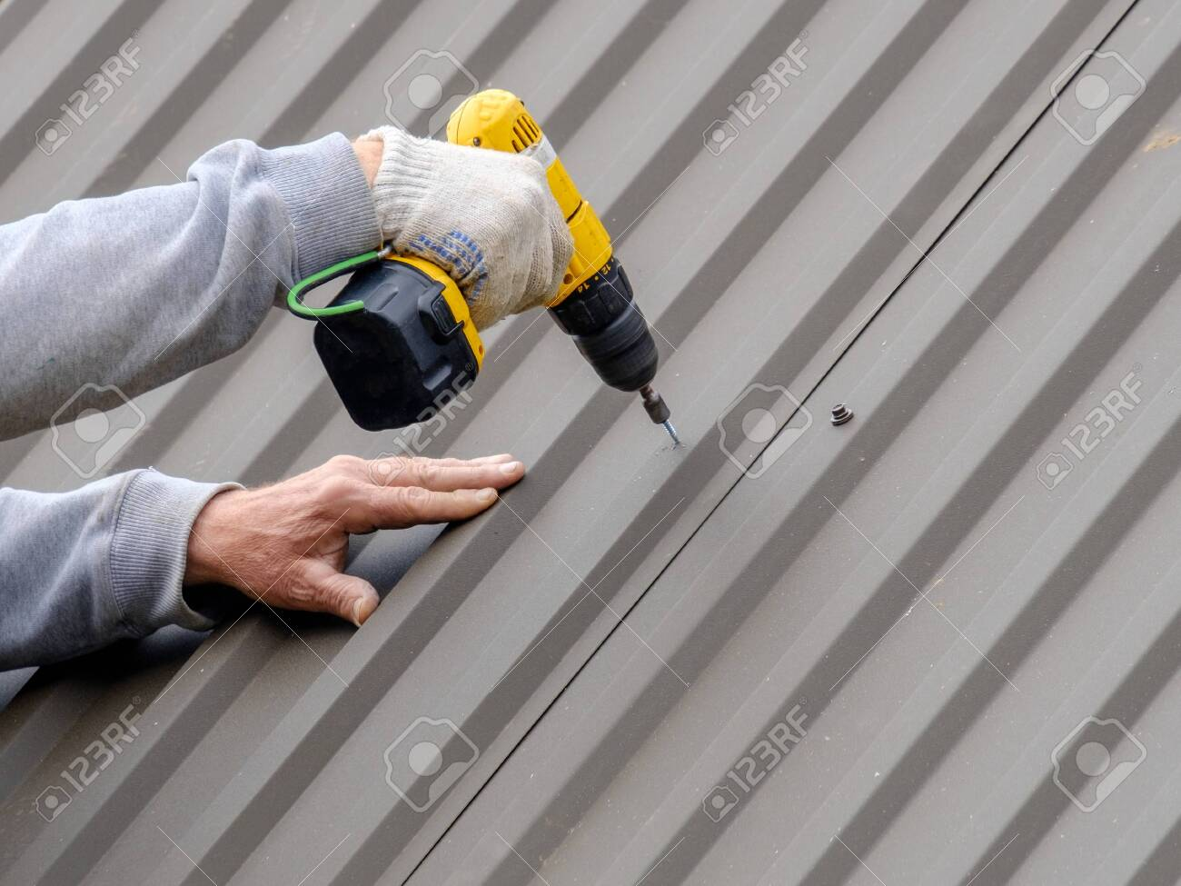 Men's hands in work gloves with a yellow screwdriver screw the roofing sheet to the roof of a country house. Cordless drill. The use of electrical engineering and technology. - 146576913