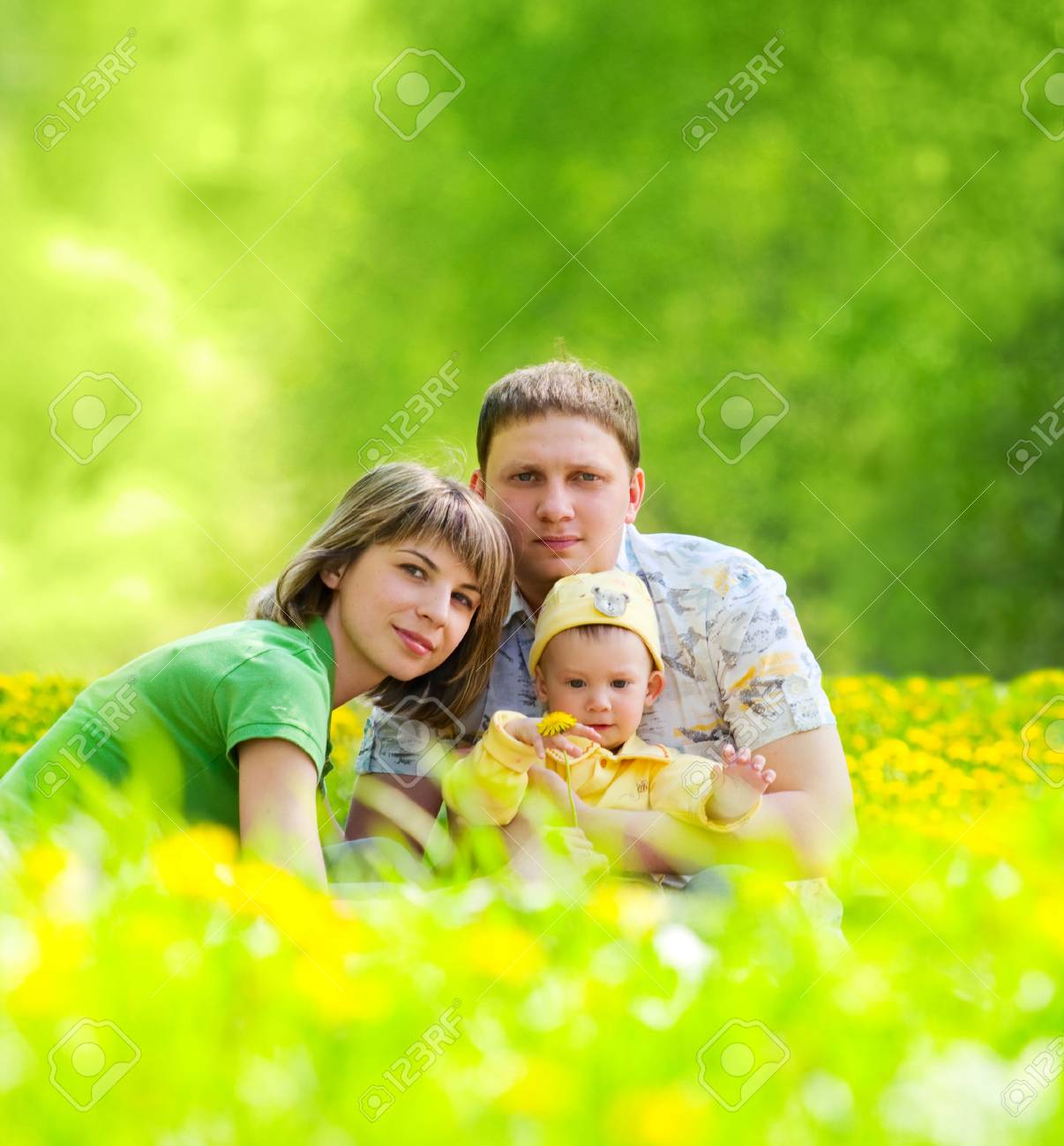 young family sitting in the grass in the park Stock Photo - 7180366