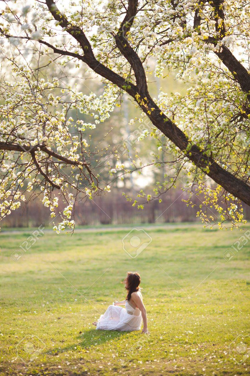 Beautiful woman sitting on the grass in summer park Stock Photo - 13773177