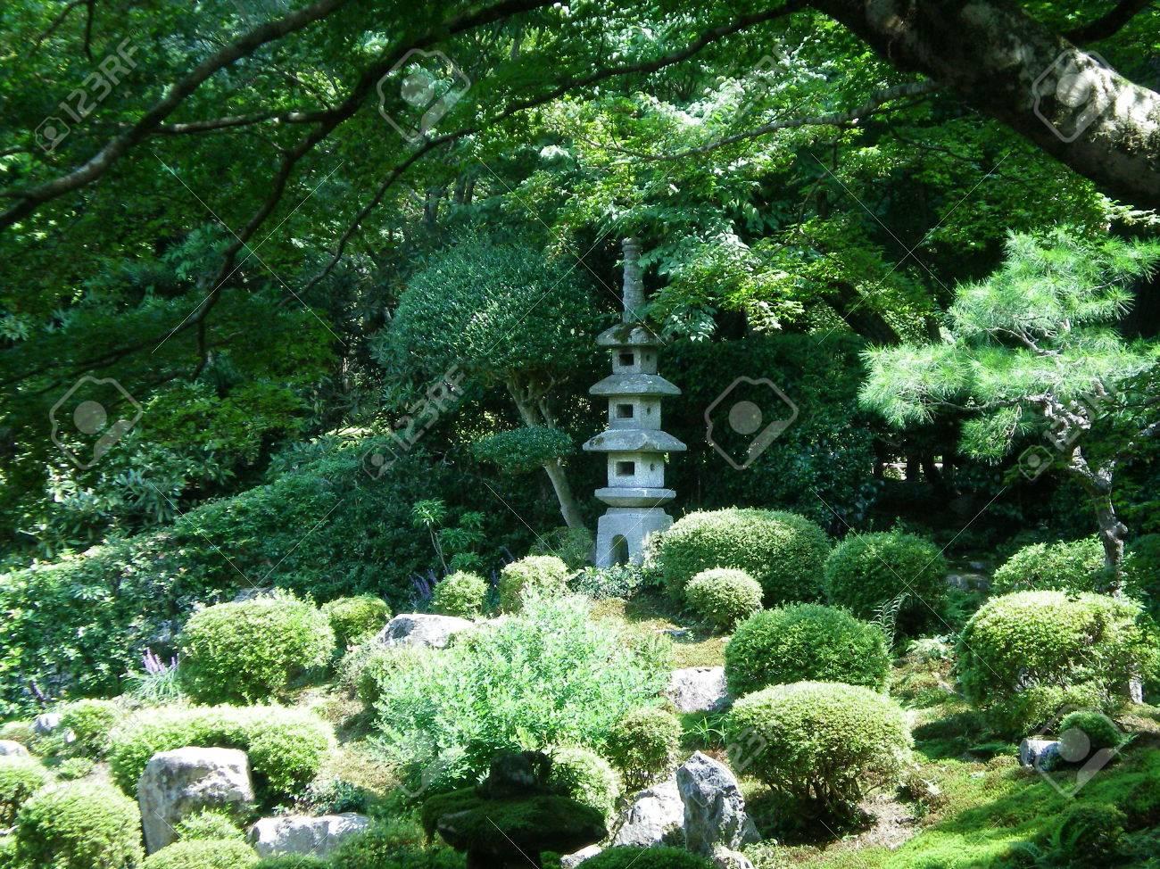 Piccoli Alberi Da Giardino un santuario di pietra giapponese in un tipico giardino formale. È  circondato da piccoli arbusti e rocce verdi potati. un albero sovrasta il  giardino.