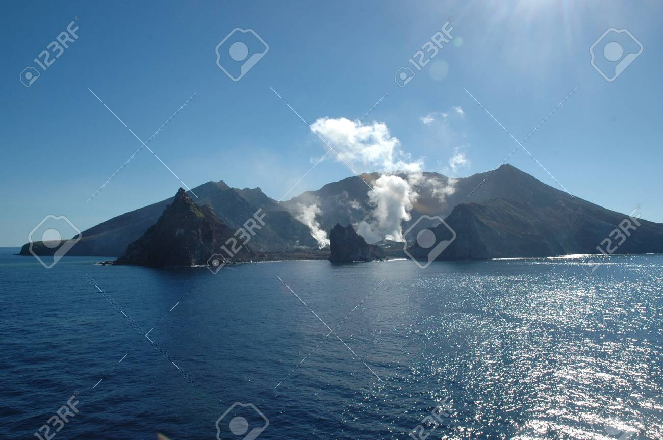 Smoke and steam rising from a volcano. It is on an island surrounded by blue sea. The sea is calm. The sky is blue, with no clouds. Stock Photo - 90320675