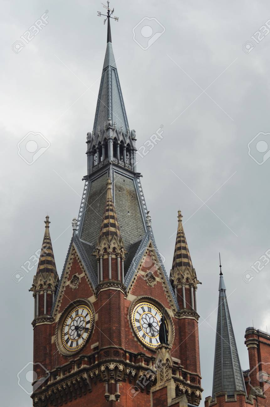 A red and cream brick clock tower is topped with a silver spire. The sky is filled with grey stormy clouds. Stock Photo - 90587532