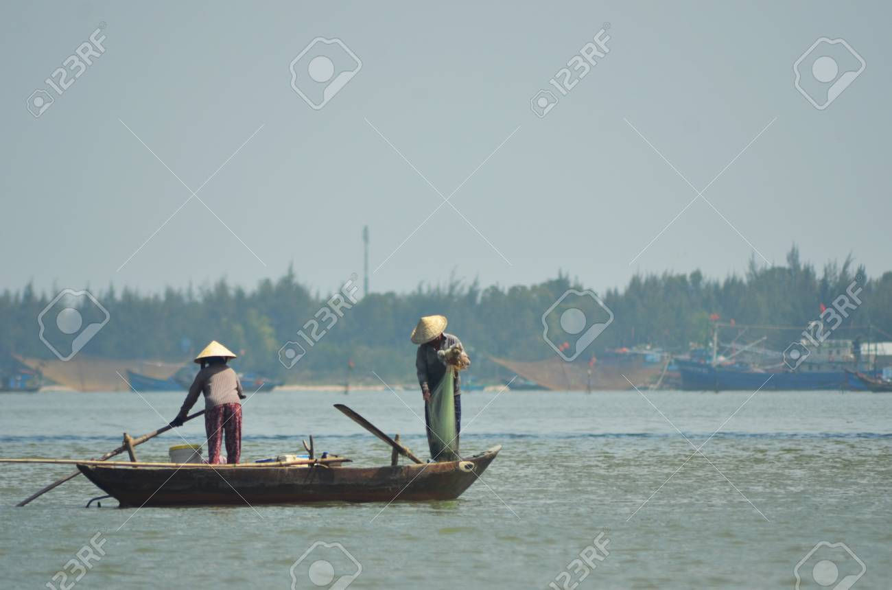 Two people on a traditional Vietnamese fishing boat. The boat has eyes painted at the front. One person is holding a net as the other steers the boat. Large nets and fishing trawlers are in the background. The sky is clear. Stock Photo - 91432602