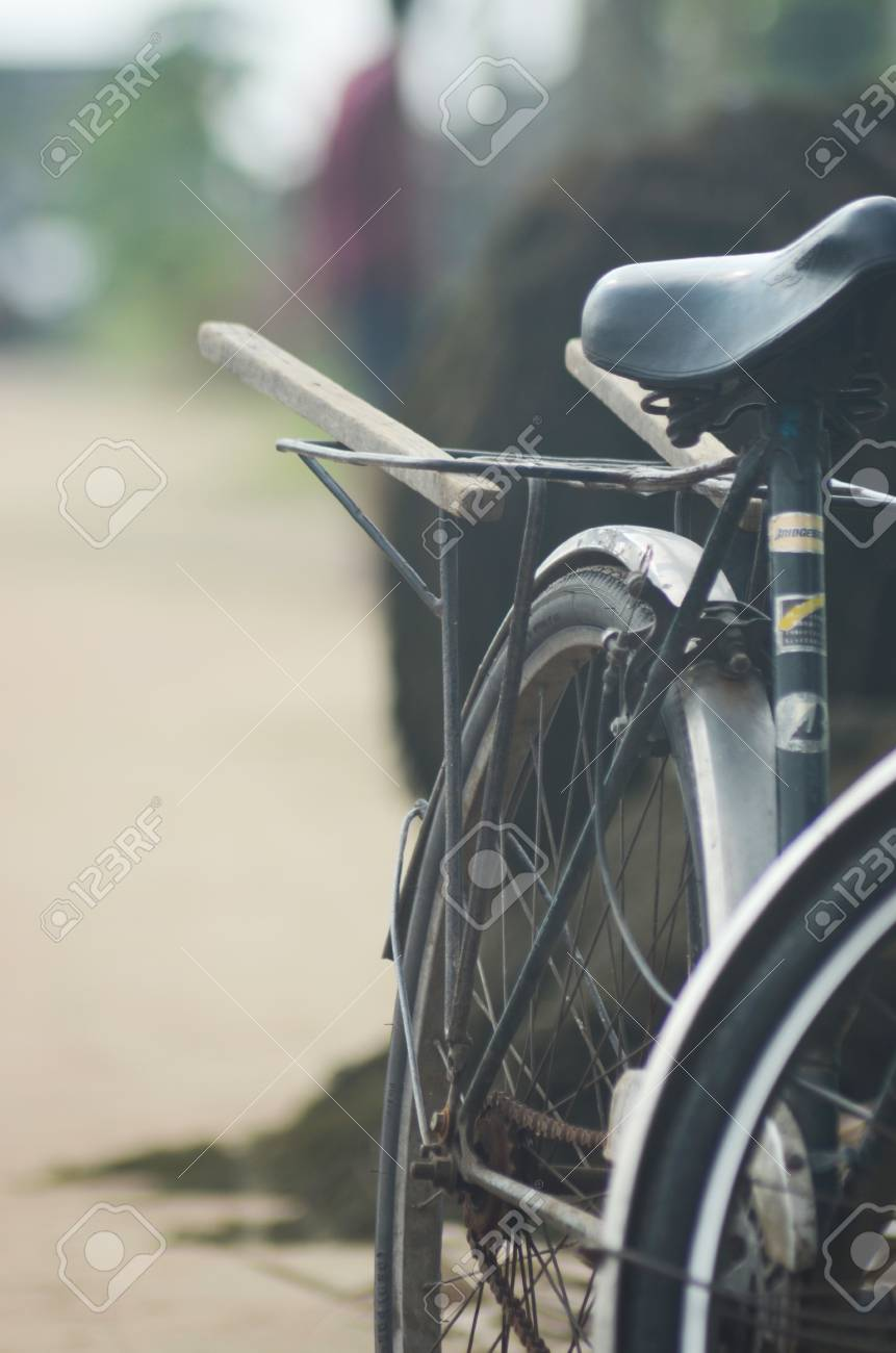 The back wheel of a stationary bicycle. A frame with two pieces of wood rests above the wheel for transporting goods. Part of the front wheel is visible. Stock Photo - 91804255