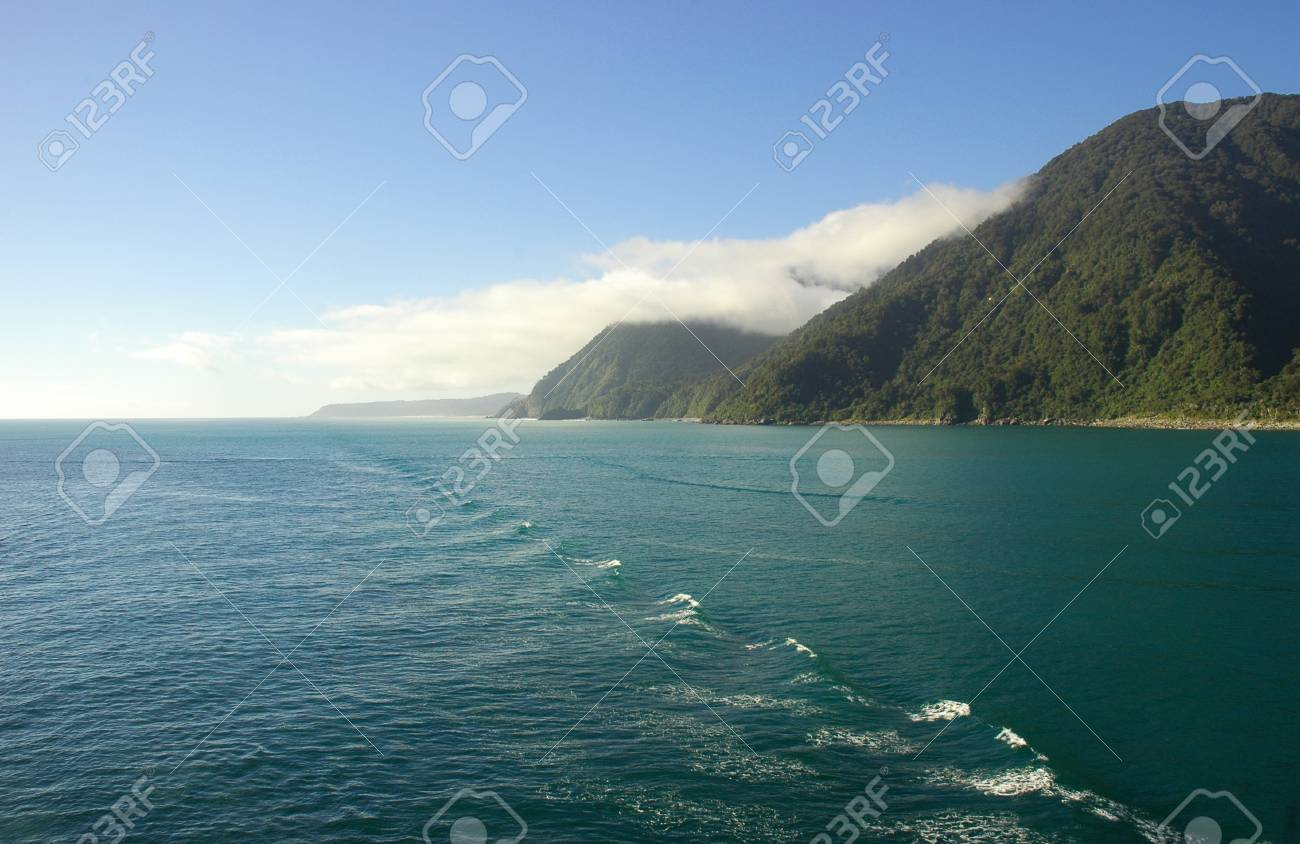 Waves from a boat spreading across the ocean. Forest covered hills run down to the shoreline. The sky is blue, with some clouds. Stock Photo - 91630665