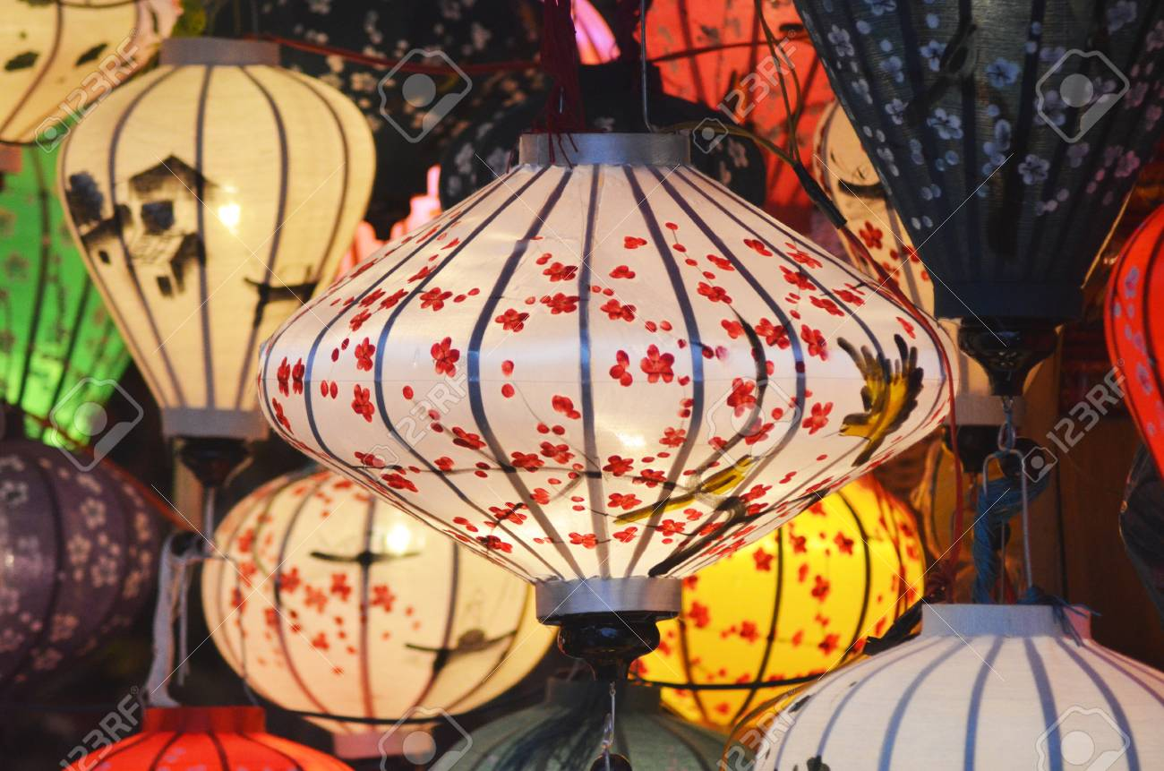 Colorful lanterns on display at a night market. They have been hand-painted, with designs of flowers, birds, and houses. They are in traditional Vietnamese style. Stock Photo - 91820446