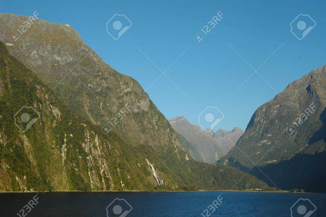 Tree-covered mountains rise from a blue lake. A waterfall can be seen. The sky is clear blue. A house is on the edge of the lake. Stock Photo - 91805791