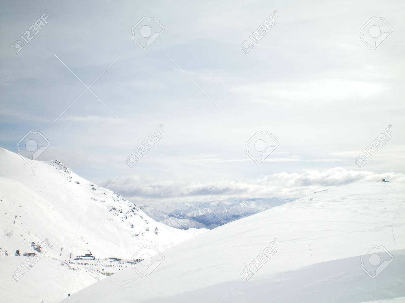 Snow covered mountains form part of a ski run. A ski resort is visible. The sky is filled with white clouds. Stock Photo - 92113027