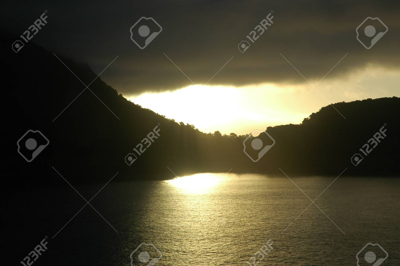 Sunlight falls through a layer of dark clouds onto a bay, turning the water golden. The hills surrounding the water are in shadow. Stock Photo - 92152043