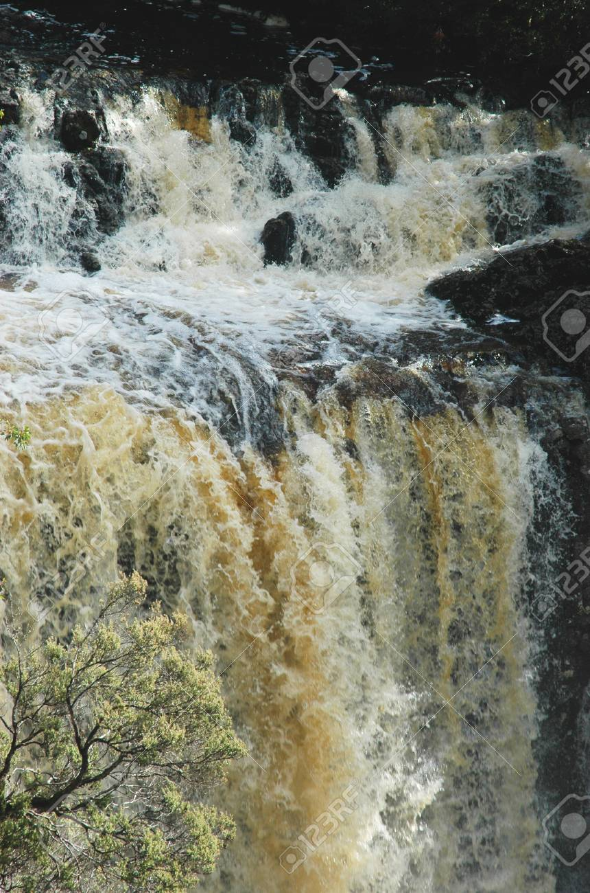 A river in flood has formed a waterfall over a cliff. The water is muddy, with white foam. A tree is in the foreground. Stock Photo - 92178863
