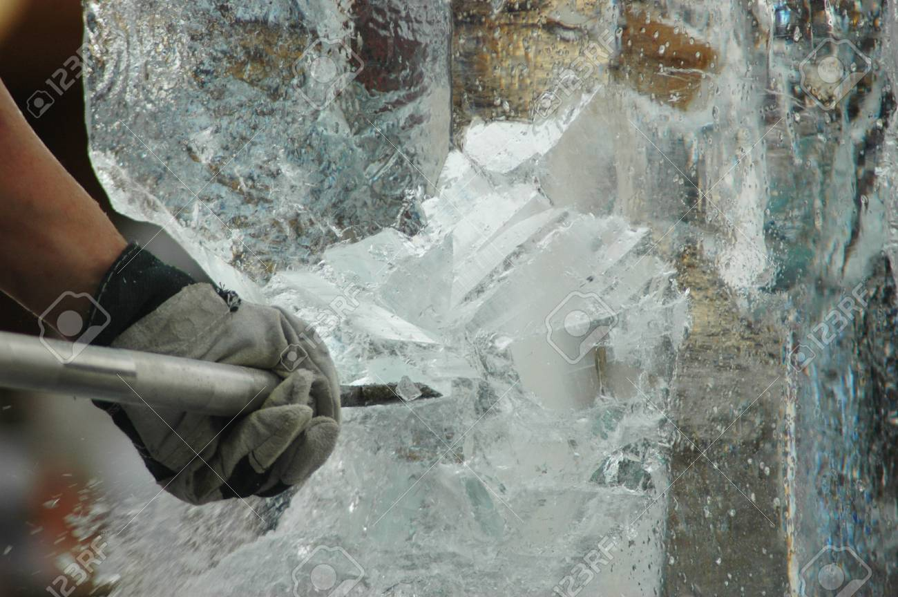 A man is carving an ice-statue from a block of ice. Only his arm can be seen. He is using an ice-pick. Shards of ice are falling from the block. Stock Photo - 92263398