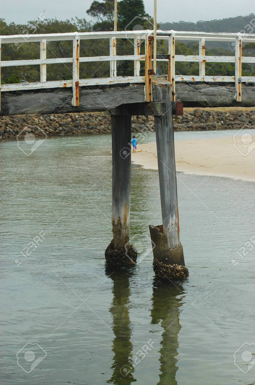 An old wooden pier stretches out from a beach. The base is covered in barnacles. A stone break water is in the distance. A child is running along the sand. Stock Photo - 92762919