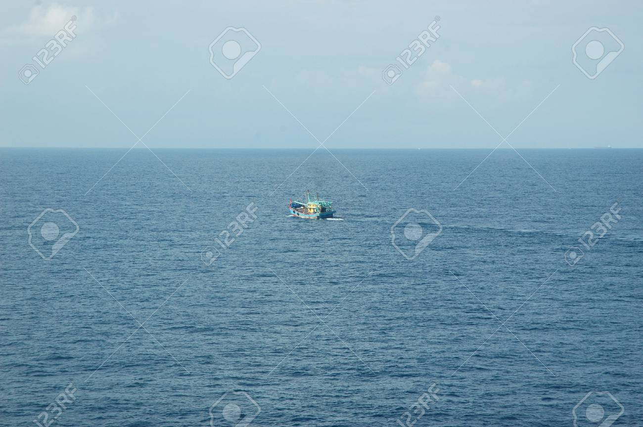 A blue fishing boat is heading out towards the horizon. It is dwarfed by the vastness of the ocean. The sea is calm, and the sky has a few faint white clouds. Stock Photo - 92905697