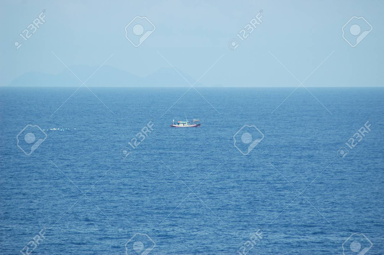 A small fishing boat being followed by a flock of seagulls. The boat looks small on the vastness of the ocean. A rocky island is rising from the horizon. The sky is clear blue. Stock Photo - 93067576