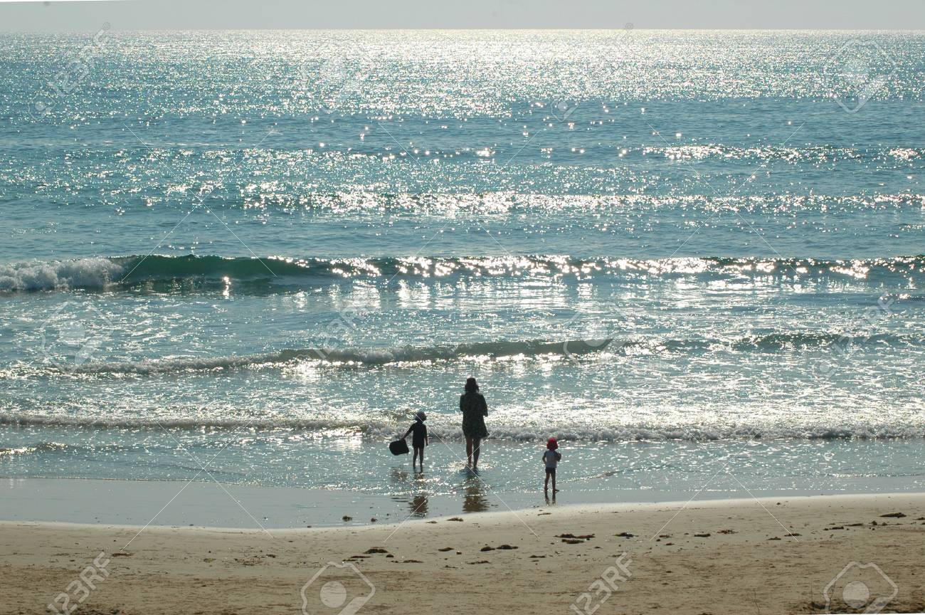 A mother is with her two young children at the beach. Stock Photo - 93055437