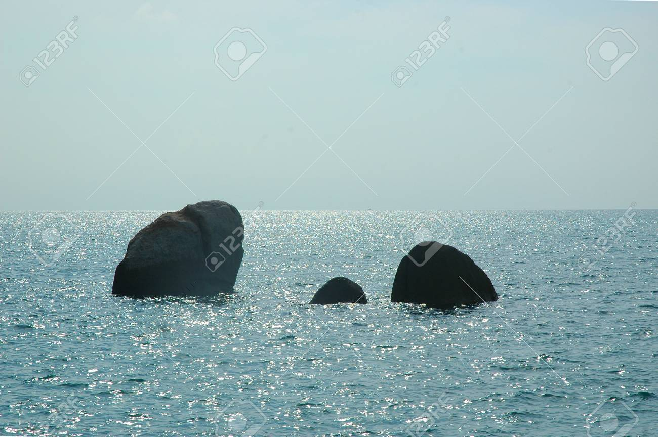 Three rocks are surrounded by an ocean which sparkles under the sunshine. The water is calm, and the sky has faint white clouds. A boat can just be seen on the horizon. Stock Photo - 93014392