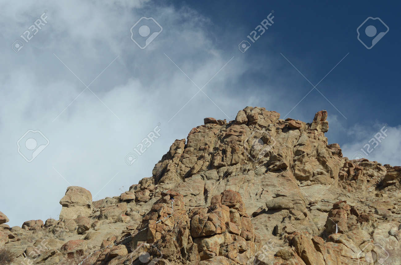 A rocky mountain slope is seen against a blue sky. A barely visible string of prayer flags tied to the rocks show the size of the boulders. The sky is blue, with wispy white clouds. - 152455361