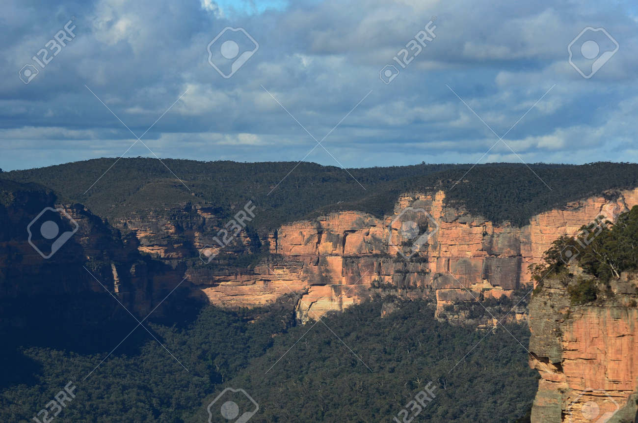 Sandstone cliffs are bathed in sunlight. They are surrounded by forest. The sky is overcast. They form part of the Megalong Valley in the Blue Mountains, Australia. - 152723795