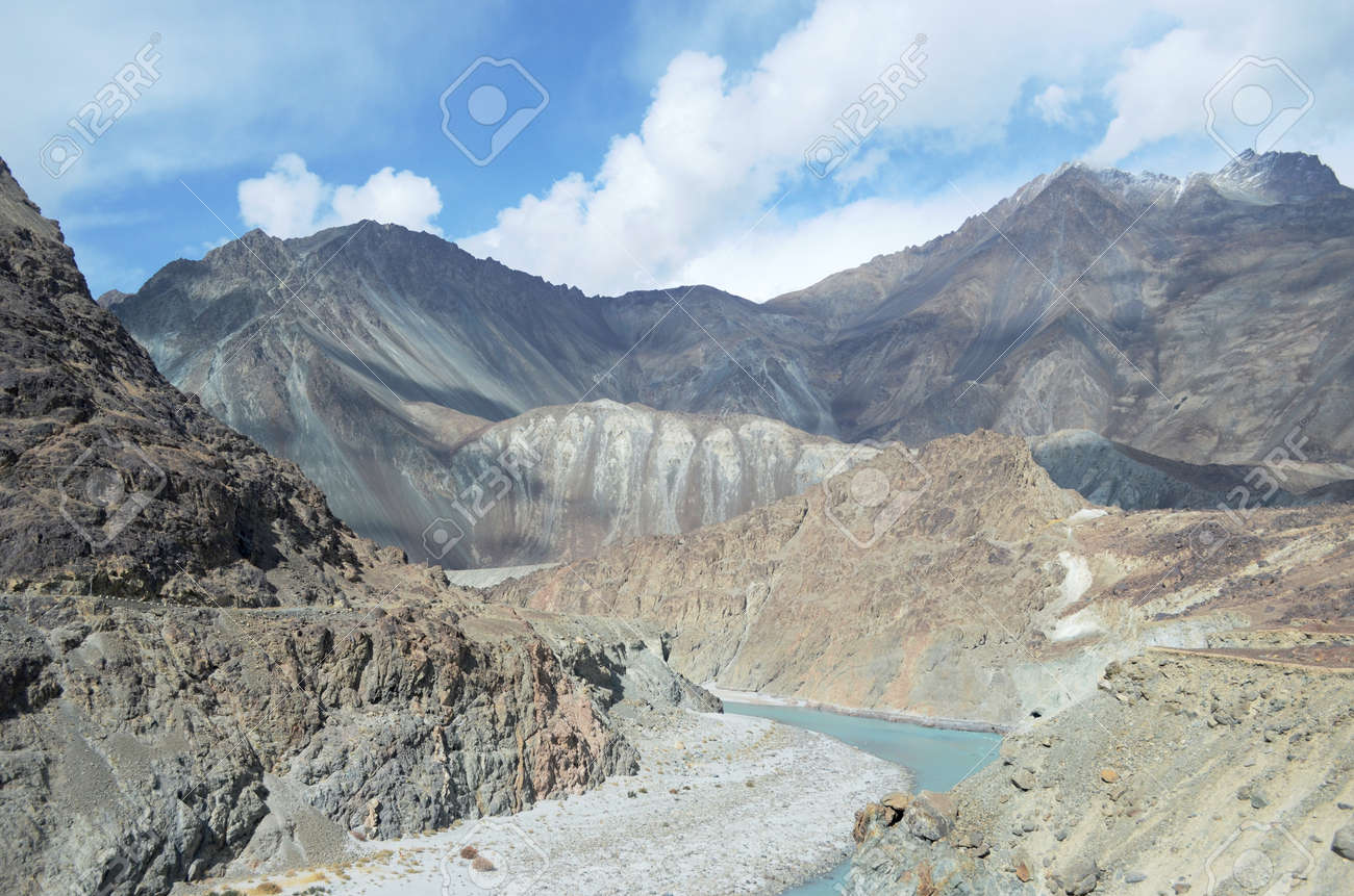 A light blue river runs through a valley bordered by rocky mountain slopes in Ladahk, India. The slopes are patterned with mineral deposits. A road is just visible on one slope. The sky is blue with white clouds. - 158251238