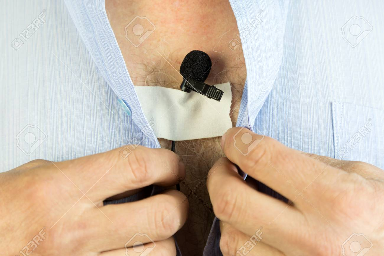A Man Attaches A Hidden Microphone To His Chest With An Adhesive