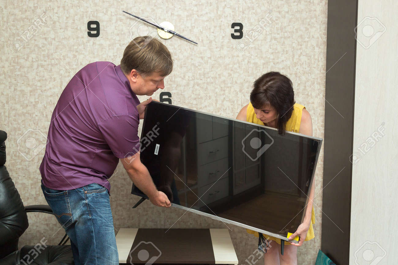 A man and a woman bring new TV into the apartment. - 171540730