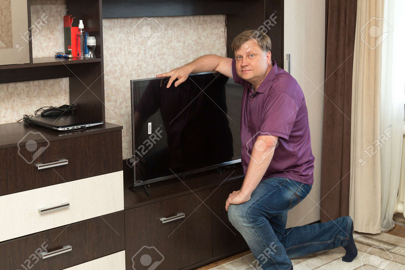 An adult man puts a new large TV in place. - 171540734