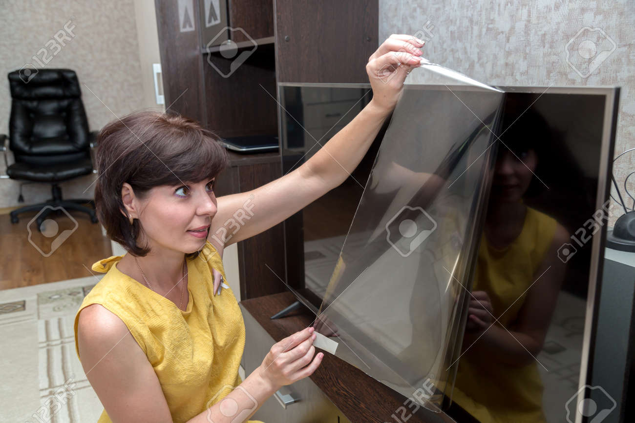 An adult brunette woman with a rainbow removes a protective film from a new lcd TV screen. - 171540739