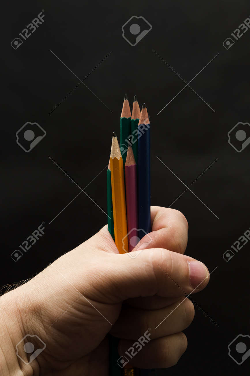 Several colored pencils in a man's fist on a gray background. - 171539779