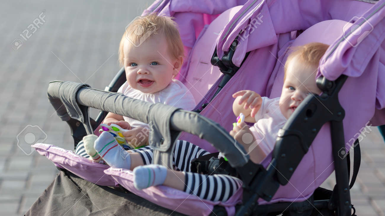 Two twin sisters are sitting next to each other in a baby stroller with toys in their hands. - 171540744