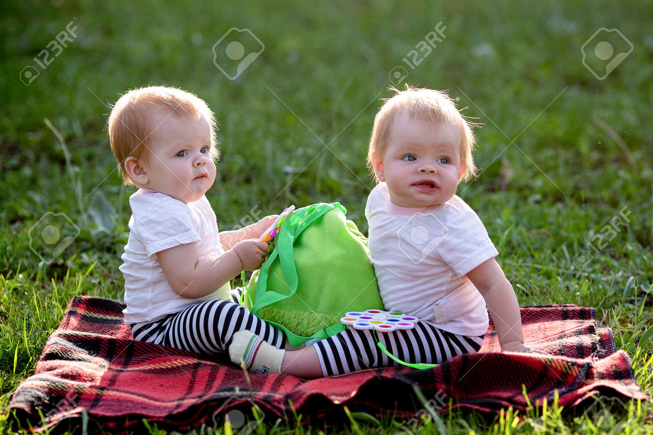 Two twin children on a blanket in park play with a children's backpack. - 171538970