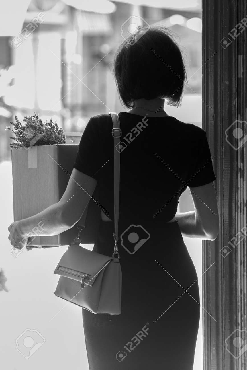 A fired brunette in a black dress with a box of personal belongings. Black and white - 171583241