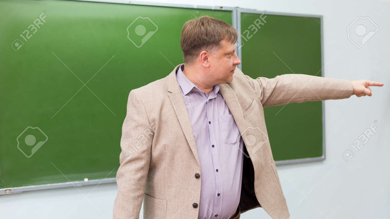 A strict teacher shows the student the exit to door from the classroom with a hand gesture. - 171582769